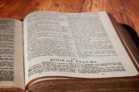 vangelo aperto: Primo piano di una vecchia Sacra Bibbia aperta al famoso libro dei Salmi su un tavolo di legno rustico. attenzione intenzionale sul titolo con profondit� di campo su sfondo. Questa traduzione � King James, che � di dominio pubblico.