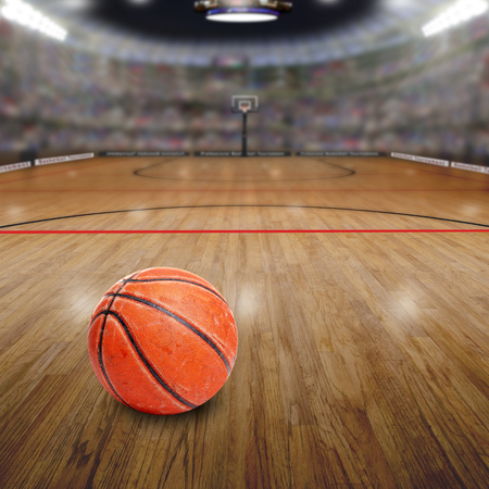 deliberate: Fictitious basketball arena full of fans in the stands with ball on court and copy space. Deliberate focus on seasoned basketball and shallow depth of field on background. Stock Photo