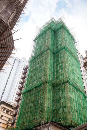 Traditional bamboo scaffolding surrounds a building under construction in Hong Kong, China. Bamboo scaffolding is popular in the countrys building industry since the 1800s. In Hong Kong where tall, skinny buildings shoot up daily, more than five million