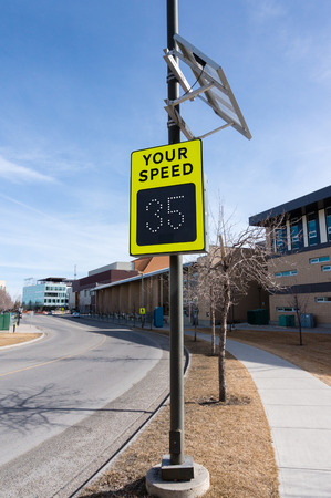 warns: Solar-powered speed indicator sign on a residential street. The sign has a sensor that warns motorists who exceed the residential street speed limit.