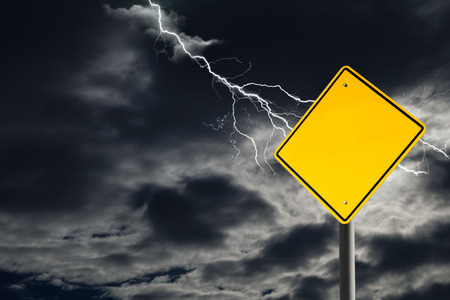 danger ahead: An empty traffic sign against a dark, cloudy and thunderous sky. Conceptually warning of danger ahead. Blank sign for copy space and message. Stock Photo