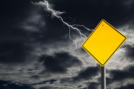 Ein leeres Verkehrszeichen gegen einen dunklen, bewölkten und donnernden Himmel. Konzeptionell vor Gefahren warnen. Leeres Zeichen für Kopienraum und -mitteilung. Standard-Bild