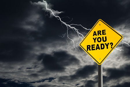 a sign: Are You Ready road sign against a dark, cloudy and thunderous sky. Conceptually warning of danger ahead.