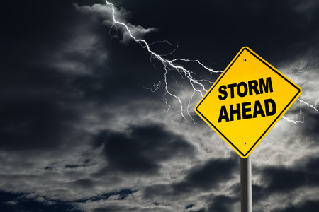 road warning sign: Storm Ahead warning sign against a dark, cloudy and thunderous sky. Concept of political storm, personal crisis, or imminent danger ahead. Stock Photo