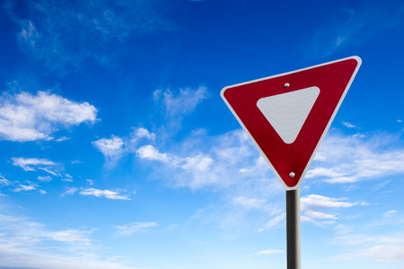 yield sign: Conceptual yield sign against a blue cloudy sky.