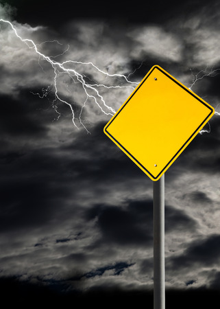 orientation: Empty sign against a dark, cloudy and thunderous sky. Conceptually warning of danger ahead. Blank sign for copy space and message. Vertical orientation