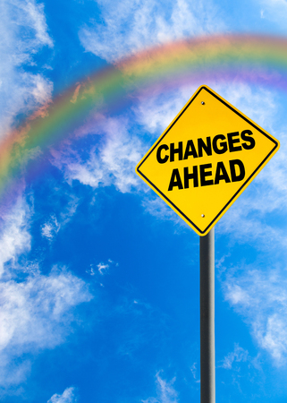 vertical orientation: Changes Ahead sign against a blue sky with rainbow and copy space. Concept of situation changing for the better. Vertical orientation. Stock Photo