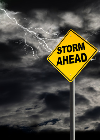 Storm Ahead warning sign against a dark, cloudy and thunderous sky. Concept of political storm, personal crisis, or imminent danger ahead. Vertical orientation