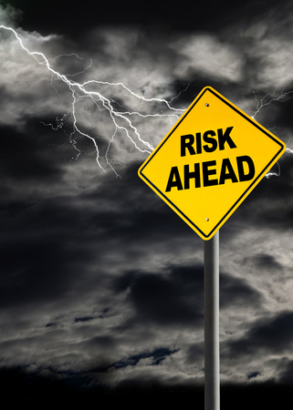Risk Ahead warning sign against a dark, cloudy and thunderous sky. Concept of political storm, personal crisis, or imminent danger ahead. Vertical orientation 免版税图像