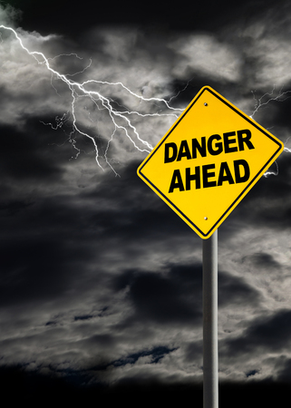 vertical orientation: Danger Ahead sign against a dark, cloudy and thunderous sky. Conceptually warning of danger ahead. Blank sign for copy space and message. Vertical orientation