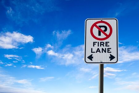 parking violation: A Fire Lane No Parking sign against a blue cloudy sky with copy space. Horizontal orientation. Stock Photo