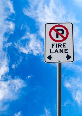 no parking sign: A Fire Lane No Parking sign against a blue cloudy sky with copy space. Vertical orientation.