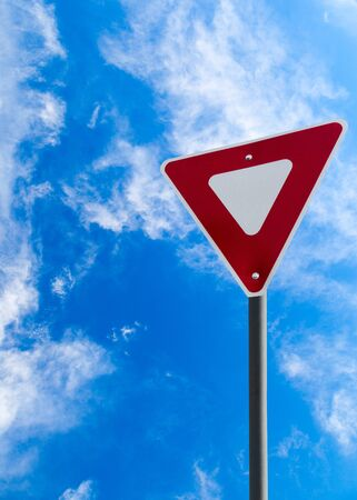 give way: Traffic yield sign against a blue cloudy sky with copy space. Vertical orientation.