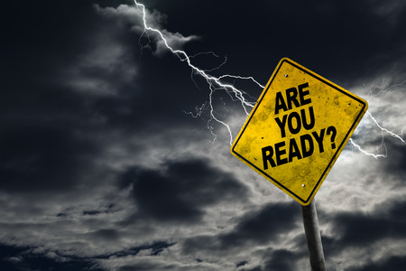 Are You Ready sign against a stormy background with lightning and copy space. Dirty and angled sign adds to the drama.