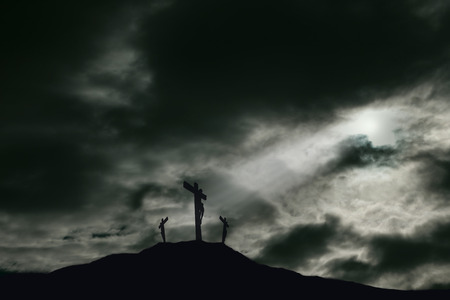 risen christ: A depiction of the crucifixion of Jesus Christ on a cross with 2 other robbers nearby on Calvary. The sky is darkened with rays of light breaking through the clouds onto the cross for drama. Concept of the death of Jesus on Good Friday and His resurrectio Stock Photo