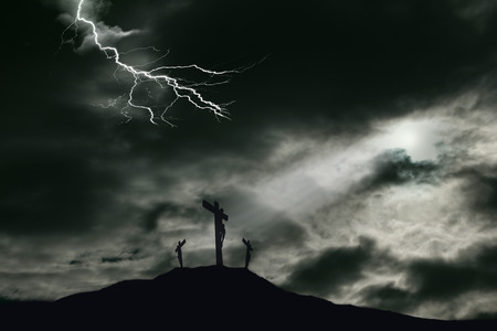 A depiction of the crucifixion of Jesus Christ on a cross with 2 other robbers nearby on Calvary. The sky is darkened with lightning and rays of light break through the clouds onto the cross for drama. Concept of the death of Jesus on Good Friday and His