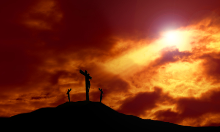A depiction of the crucifixion of Jesus Christ on a cross with 2 other robbers against a dramatic sunset with rays of light breaking through the clouds onto the cross and lens flare for effect. Concept of the death of Jesus on Good Friday and His resurrec