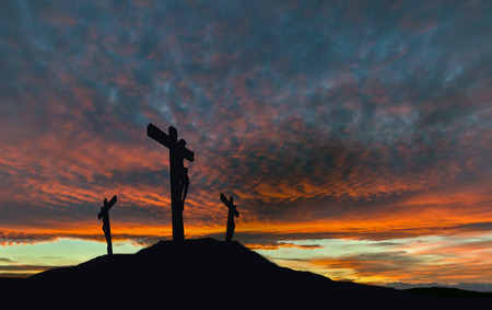 A silhouette of the crucifixion of Jesus Christ on a cross with 2 other robbers against a dramatic sunset. Concept of the death of Jesus on Good Friday and His resurrection on Easter Sunday. Horizontal orientation with copy space.