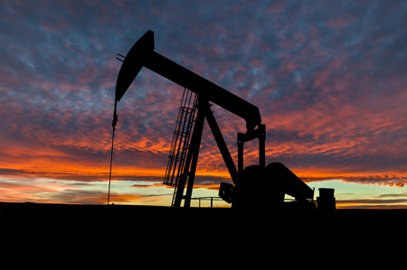 jacks: Dramatic sky over a pumpjack in rural Alberta, Canada. These jacks can extract between 5 to 40 litres of crude oil and water emulsioin at each stroke.