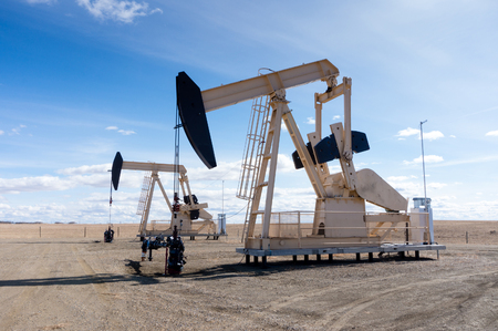 A pair of pumpjacks extracting oil out of an overground well in rural Alberta, Canada. These jacks can extract between 5 to 40 litres of crude oil and water emulsioin at each stroke.