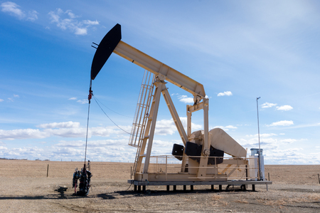 A pumpjack extracting oil out of an overground well in rural Alberta, Canada. These jacks can extract between 5 to 40 litres of crude oil and water emulsioin at each stroke.