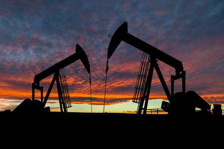 Dramatic sky over two pumpjacks in rural Alberta, Canada. These jacks can extract between 5 to 40 litres of crude oil and water emulsioin at each stroke.