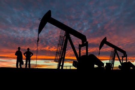 극적인 하늘을 석유 유전 pumpjack 사이트에서 석유 근로자의 실루엣.