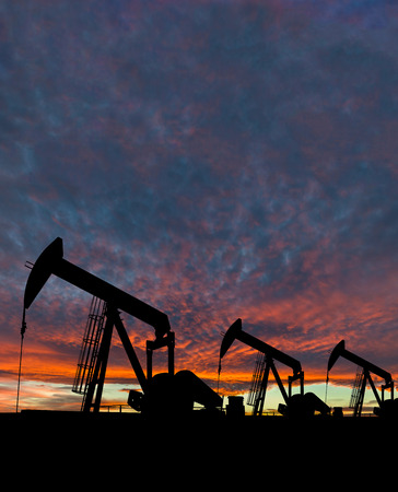 vertical orientation: Silhouette of pumpjack at an oil field against a dramatic sky. Vertical orientation with copy space.