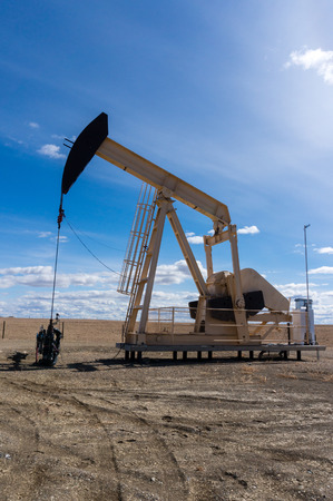 PUMPER: A pumpjack extracting oil out of an overground well in rural Alberta, Canada. These jacks can extract between 5 to 40 litres of crude oil and water emulsioin at each stroke. Vertical orientation. Stock Photo