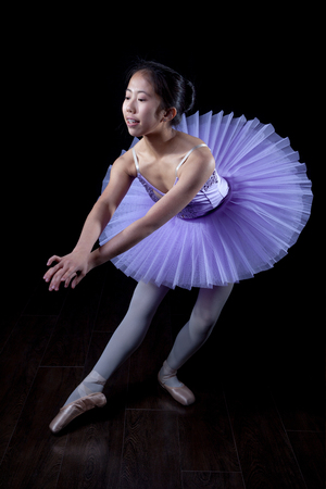 pointe shoes: Young Ballerina wearing pointe shoes and tutu in dance pose. Stock Photo