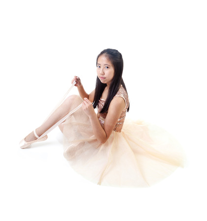 pointe shoes: Young and beautiful Asian ballerina tying her ballet pointe shoes. Isolated on white background.