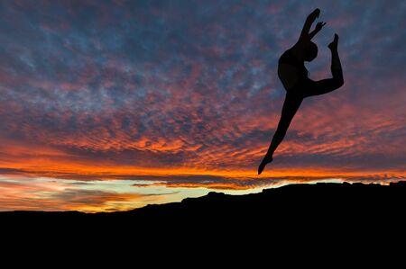 iluminado a contraluz: Silueta de mujer bailando y haciendo ejercicio en la cima de la montaña con el cielo puesta de sol en el fondo. Foto de archivo