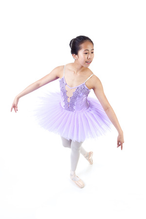 pointe shoes: Young Asian ballerina with braces wearing purple tutu and pointe shoes dancing. Isolated on white background.