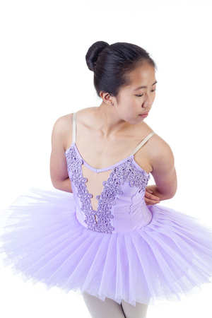 purple shoes: Young Asian ballerina wearing purple tutu and pointe shoes dancing. Isolated on white background.