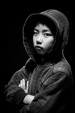 Asian boy in hoodie jacket staring at camera. Black and white shot in studio with back lighting for highlights.