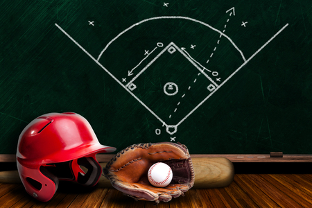 Baseball equipment consisting of glove, helmet, bat and baseball with background play strategy drawn on chalk board with copy space.