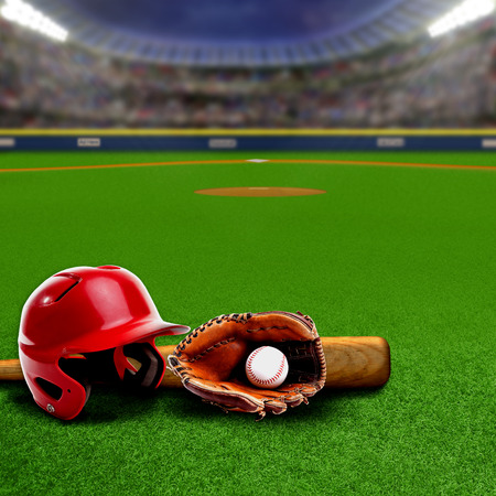 Baseball stadium full of fans in the stands with baseball helmet, bat, glove and ball on the field. Deliberate focus on equipment and foreground with shallow depth of field on background. Floodlights flare for effect and copy space.