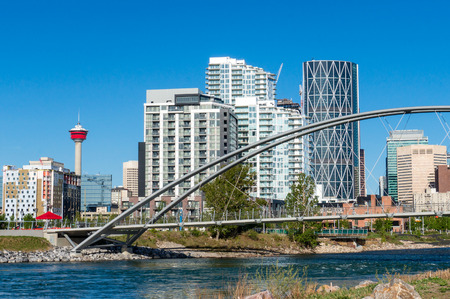 Calgary downtown as viewed from St. Patrick's Island at East Village, with the George C King Bridge across the Bow River. The iconic Calgary Tower can be seen in the background.