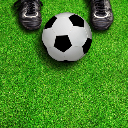 football cleats: Player standing on field showing soccer cleats with ball and copy space below. Stock Photo