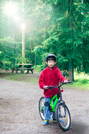 deliberate: An Asian boy riding his bike in an outdoor park. Backlit by morning sunlight in background with deliberate lens flare for effect. Vertical orientation with copy space. Stock Photo
