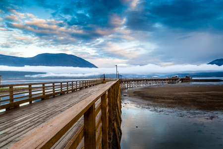 longest: British Columbias Salmon Arm wharf on a cloudy morning at sunrise, with low fog on the horizon. It is the longest wooden wharf in North America.