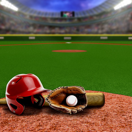 floodlights: Baseball stadium full of fans in the stands with baseball helmet, bat, glove and ball on infield dirt clay. Deliberate focus on equipment and foreground with shallow depth of field on background. Floodlights flare for effect and copy space. Stock Photo