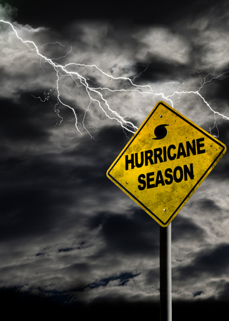 Hurricane season with symbol sign against a stormy background and copy space. Dirty and angled sign adds to the drama. Vertical orientation.