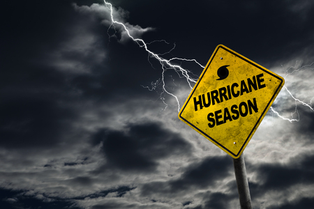 adds: Hurricane season with symbol sign against a stormy background and copy space. Dirty and angled sign adds to the drama. Stock Photo