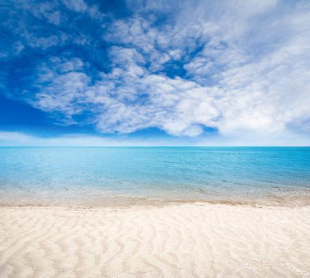 닫기 바다와 하늘 배경에 필드의 얕은 깊이와 여름 하루에 전경 모래 해변을 닫습니다.