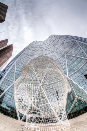 CALGARY, CANADA - June 14: Wonderland sculpture by Jaume Plensa in the front of the Bow Tower on June 14, 2016. At 774 ft tall, The Bow is Canadas second tallest office building outside of Toronto. Jaume Plensa is a Catalan Spanish artist and sculptor.
