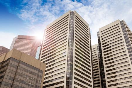 レンズ フレア青と曇り空を背景にカルガリーのダウンタウンのオフィスビルのビューを底。