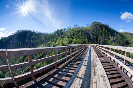 deliberate: Originally one of 19 wooden railway trestles built in the early 1900s in Myra Canyon, BC, the place is now a public park with biking and hiking trails. Deliberate sun burst and lens flare for effect. Stock Photo