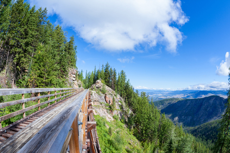 A wooden trestle in Myra Canyon, BC, offers a view of the Okanagan Valley below.