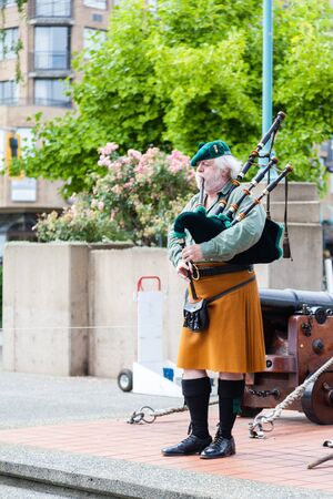 arose: NANAIMO, CANADA - JULY 9: A Scottish bagpipe player performs prior to the daily cannon firing ceremony at the historic Bastion July 9, 2016. The daily ceremony has been an attraction over the last three decades. Nanaimos Scottish tradition arose from the
